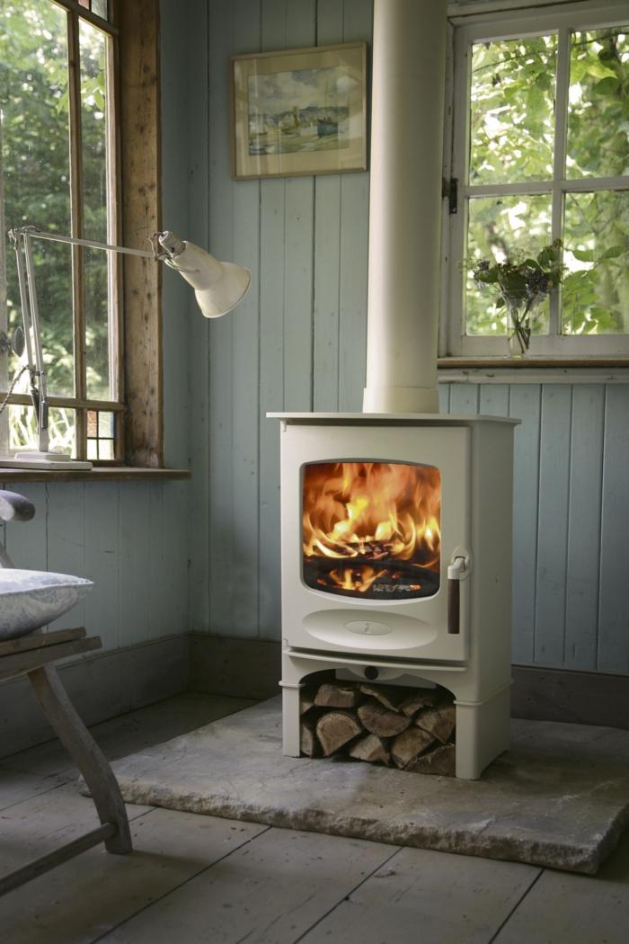 chimenea, estufa vintage en blanco, casa rural, paredes de madera pintadas en azul claro, suelo de parquet