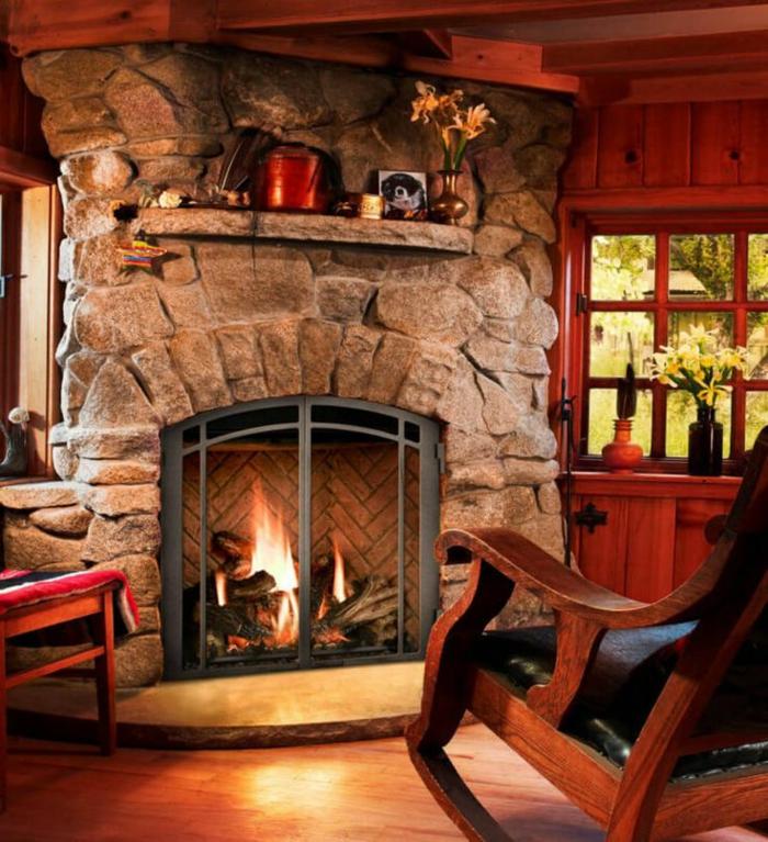 estufas de leña con horno, rincón en estilo rústico con chimenea masiva de piedra, mecedora de madera