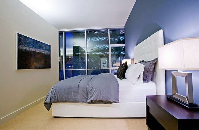 tonos de azul, habitación moderna en azul atenuado, muebles de madera y cama grande con cabecero en capitoné, ventanales con vista