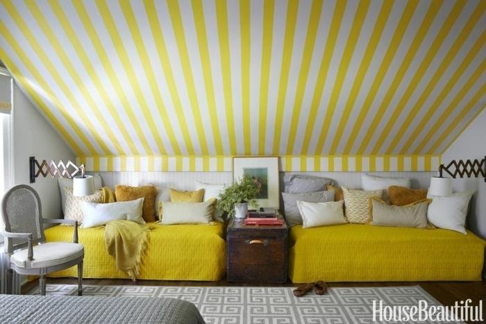 colores calidos, propuesta irresistible en amarillo mostaza y gris, dormitorio con cama y dos sofás, papel pintado en dos colores