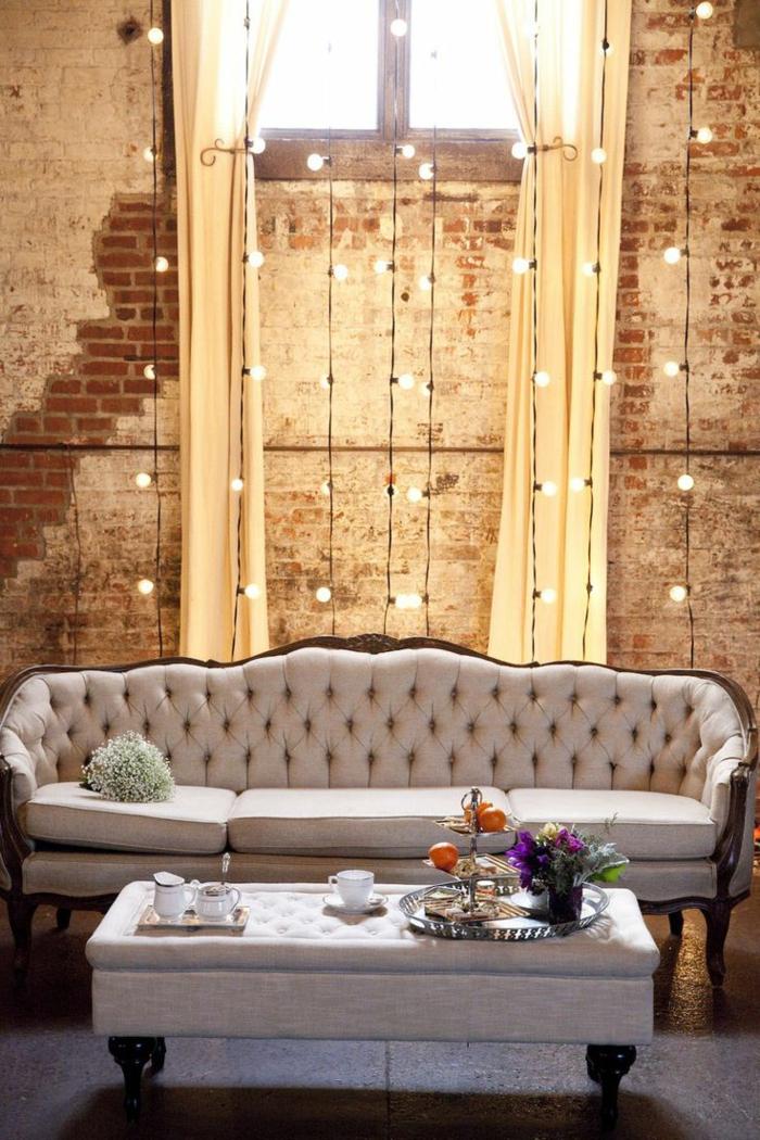revestimiento paredes, mezcla de estilo clásico e industrial. salón con sofá tapizada en capitone. pared de ladrillo con efecto desgastado, ventana alta, bombillas colgantes