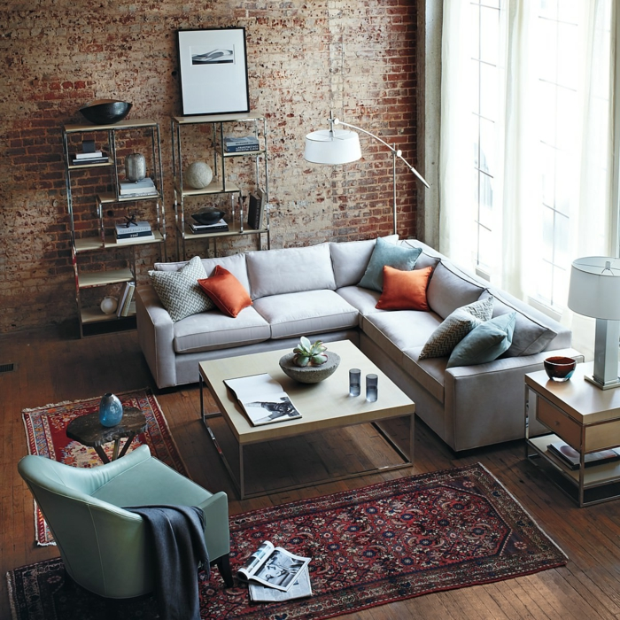 revestimiento paredes, salon fotografiado desde arriba, alfombras, sillon tapizado de piel, sofá, ventanal y pared alta de ladrillo