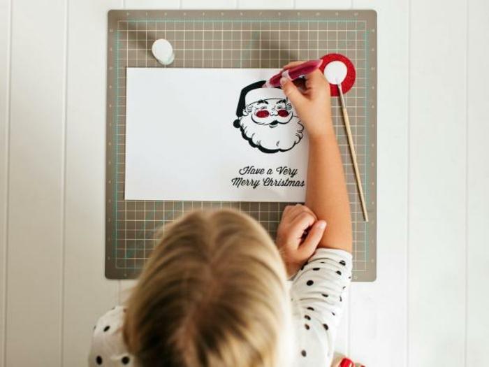 como hacer adornos de navidad, niña decorando una tarjeta de navidad con papa noel, propuestas fáciles para Navidad
