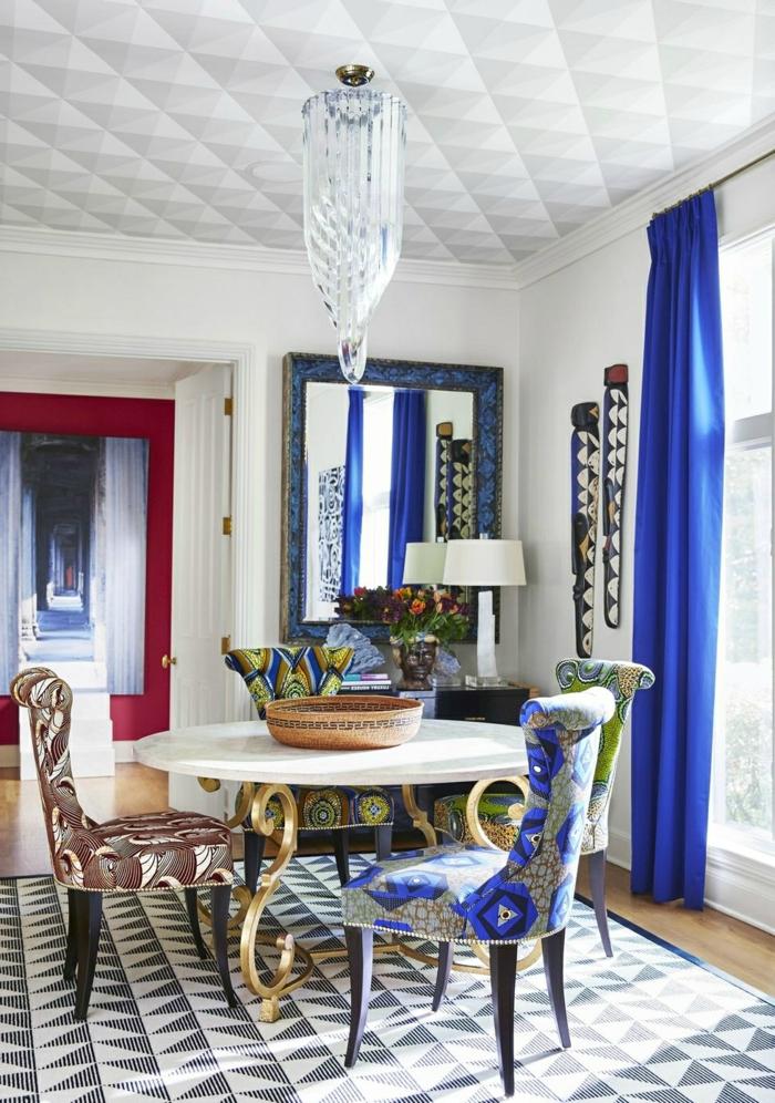 salon comedor, propuesta muy elegante de sillas tapizadas en diferentes colores, cortinas en azul intenso y lámpara muy original en el techo