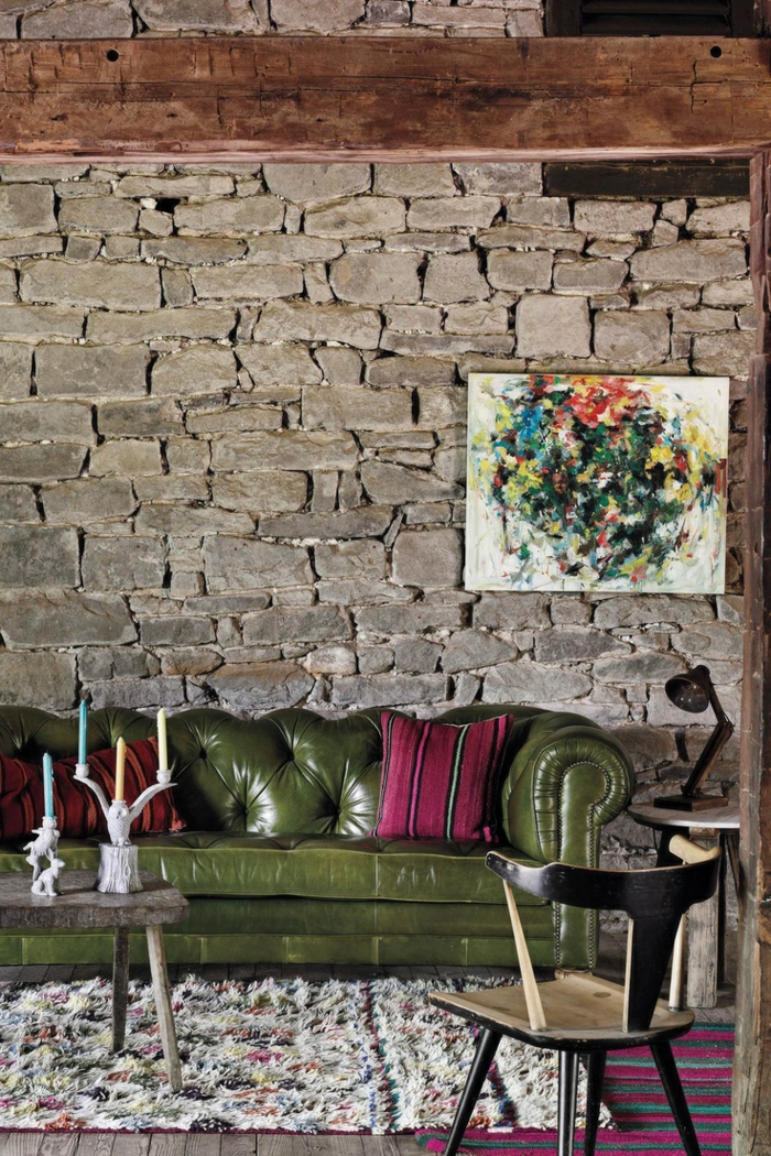 pared de piedra, salón moderno con sofá tapizada de piel, cuadro abstracto, mesa con portavelas, pared de piedra rustica