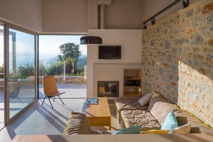 pared de piedra, salón con ventanales y mucha luz natural, colores cálidos, sofá y chimenea, media pared con panel de piedra