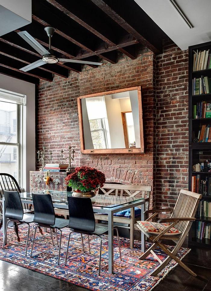 ladrillo visto, comedor en estilo industrial con vigas en el techo y lámpara ventilador, pared de ladrillo con espejo grande, sillas desparejas