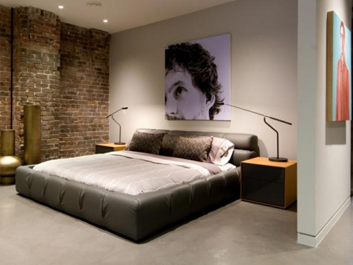 pared de piedra, dormitorio grande moderno con cama doble sin puerta, cuadro con cara de hombre, pared de ladrillo