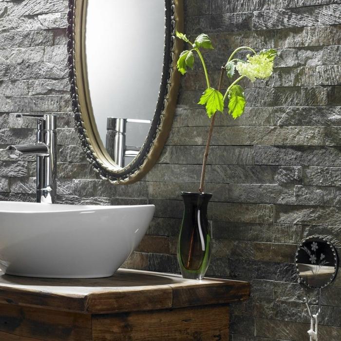 ladrillo visto, detalle de baño con lavabo blanco y espejo ovalado, jarra con planta verde, pared de piedra decorativa gris