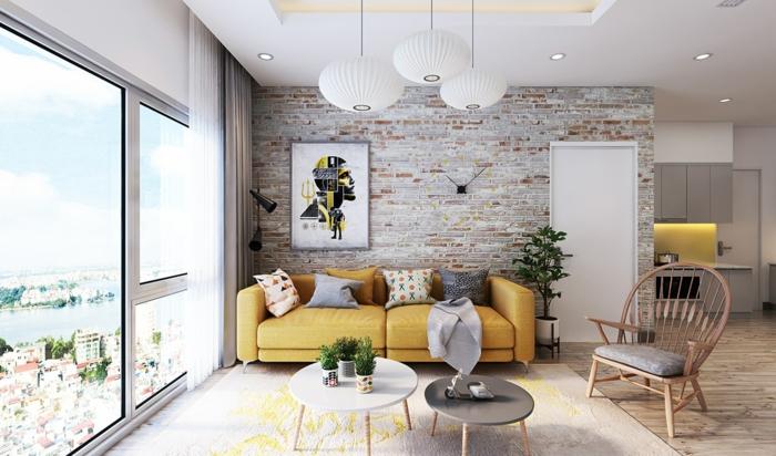 ladrillo visto, salón estilo nórdico con mucha luz, sillon y sofá amarilla con cojines, mesas redondas, lámparas colgantes, pared de ladrillo con cuadro y reloj