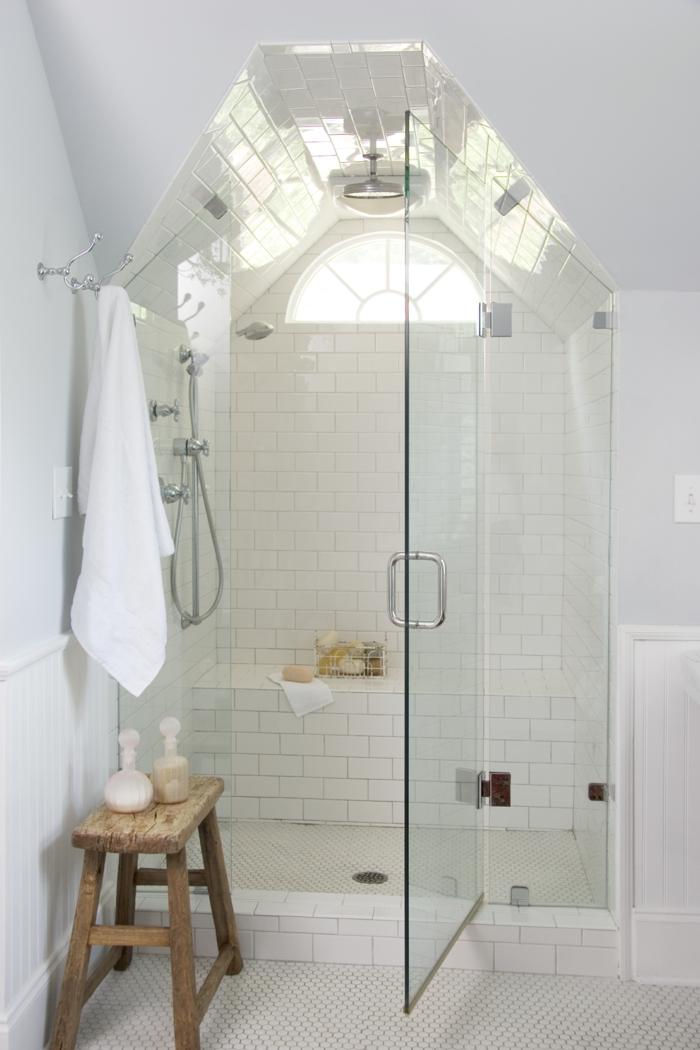 ducha de obra, baño todo blanco, techo inclinado, paredes con baldosas, ventana pequeña, ducha de obra con banco y puerta de vidrio