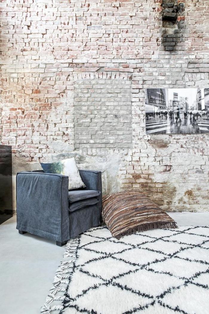 ladrillo caravista, interior minimalista con pared de ladrillo con aspecto desgastado, sillón azul y foto en blanco y negro