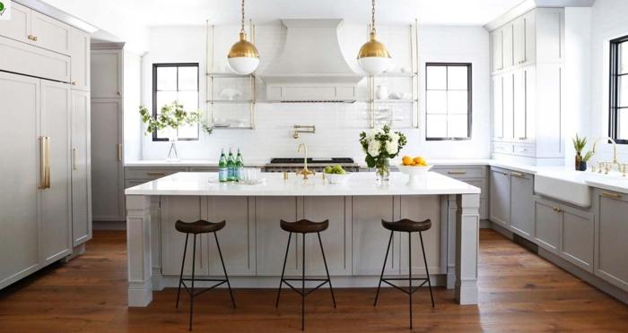 cocinas con barra, grande cocina en blanco con detalles dorados y suelo de madera, sillas vintage de tres patas