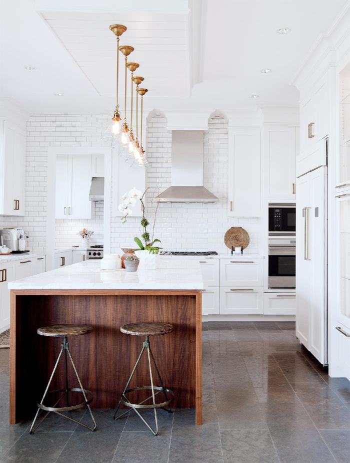 cocinas con barra, cocina en blanco con grande barra de madera, lámparas colgantes con elementos dorados, campanas extractora metálica