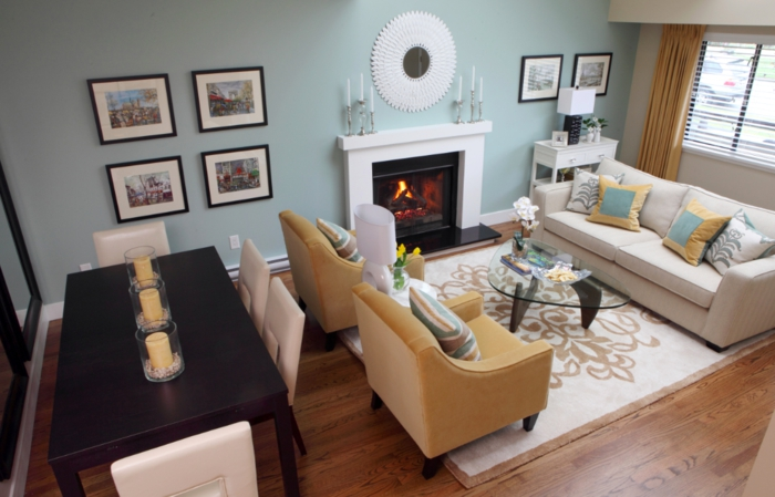 muebles de salon modernos, salon acogedor con rincón para comer mesa de madera decorada con velas y sillas en beige, paredes en azul claro, sofás en beige