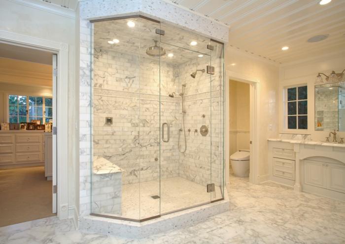 duchas de obra, baño de mármol con ducha de obra delimitada con paredes y vidrio, ducha efecto lluvia, suelo con láminas de madera