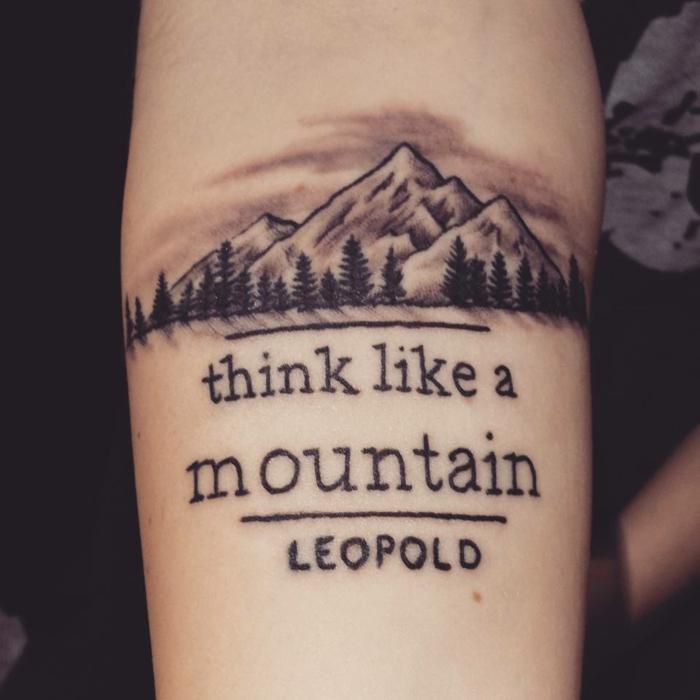tipos de tatuajes, tatuaje de antebrazo para mujeres con montaña, pinos y cita con letras negras