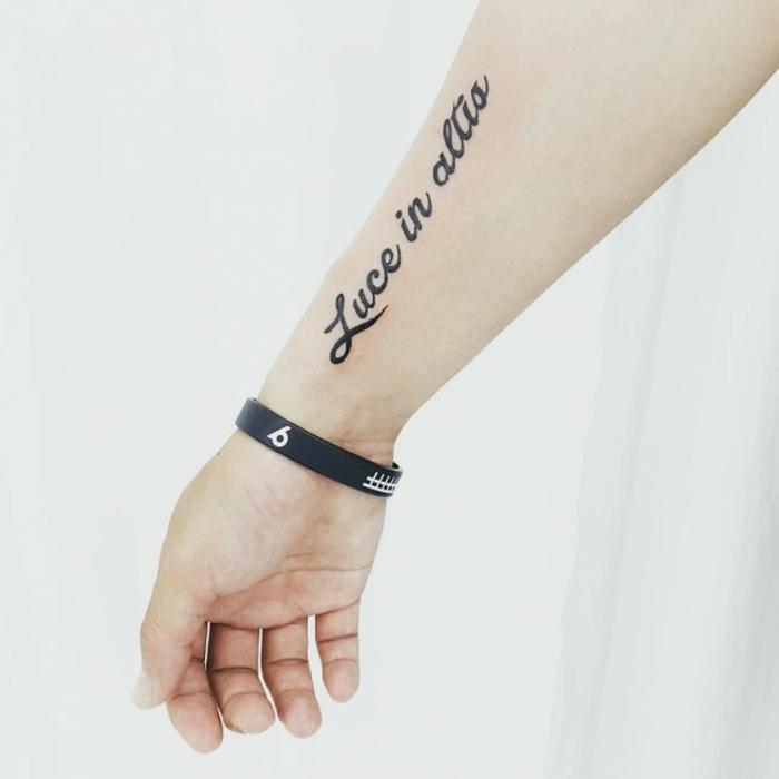 tatuajes mujer, tatuaje delicado con frase para el antebrazo, letras negras en cursiva, mano con pulsera negra