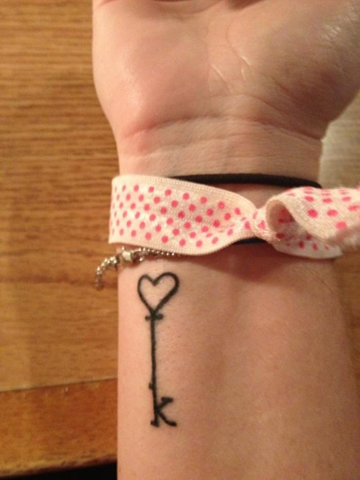 tatuajes letras, tatuaje delicado para mujer, muñeca con tatuaje de letra K y corazon en negro, pulseras