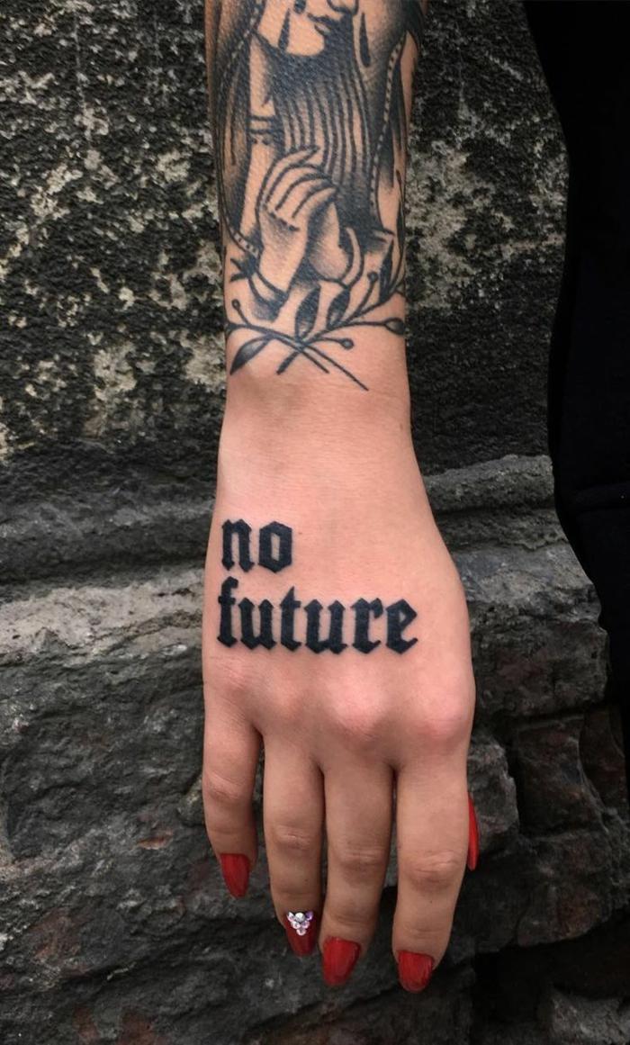 tatuajes letras, con tatuaje de antebrazo y mano, tatuaje con frase de letras en bloque negras, uñas con esmalte rojo
