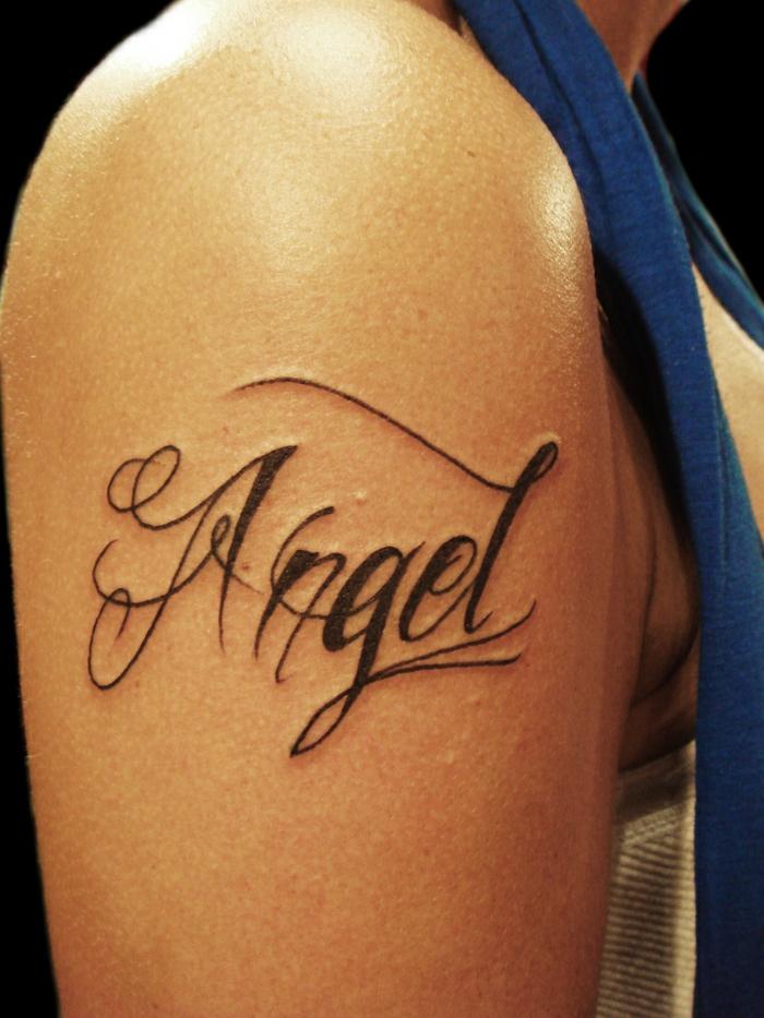 tatuajes letras, mujer con tatuaje en el brazo, tatuaje de nombre con letras negras en cursiva con adornos