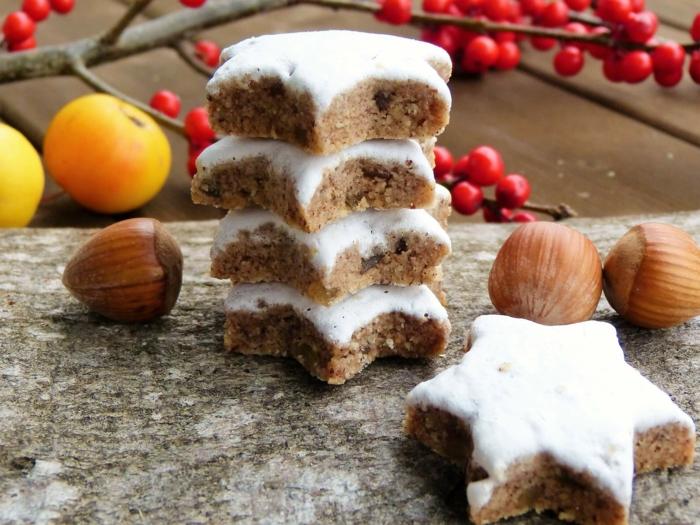 estrellas navidad, galletas navideñas con canela espolvoreadas con azúcar glass, acebo manzanas y avellanas