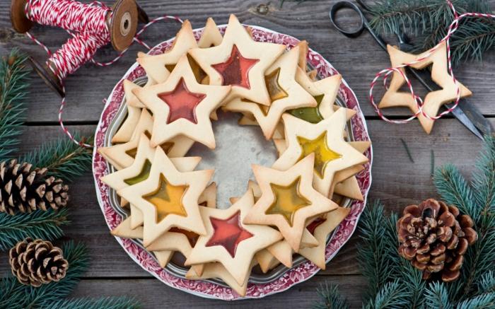estrella navidad, galletas estrellas con gelatina en rojo y amarillo, decoración de piñas y ramos de pino, carretes de hilo