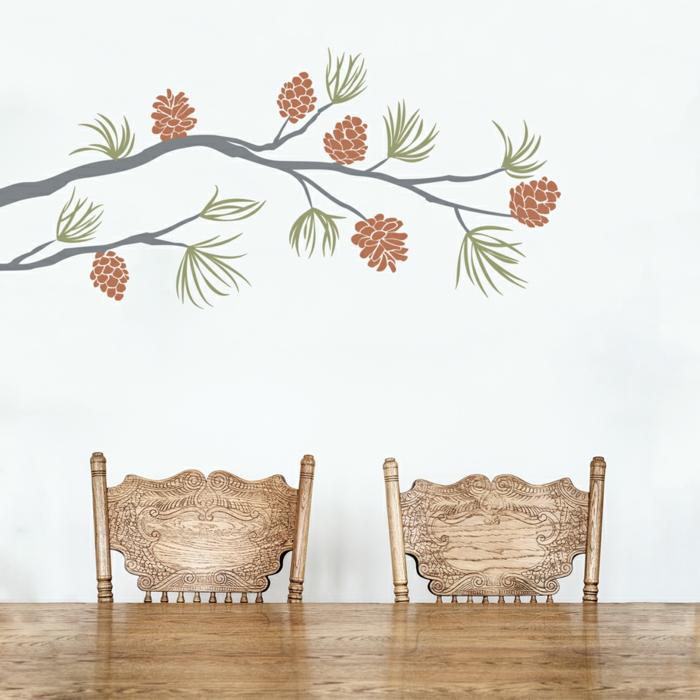 decoracion paredes, vinil como ramos de pino en gris, verde y marrón sobre pared blanca, comedor con sillas artesanales,