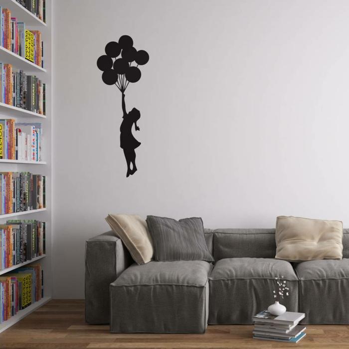 decoracion paredes, sala de estar con sofá y librería, pared blanca con vinilo con graffiti de Banksy la chica con los globos