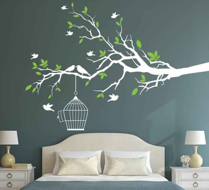 vinilos infantiles, dormitorio con cama doble, pared en azul oscuro, vinilo con rama de árbol en blanco y verde con pájaros