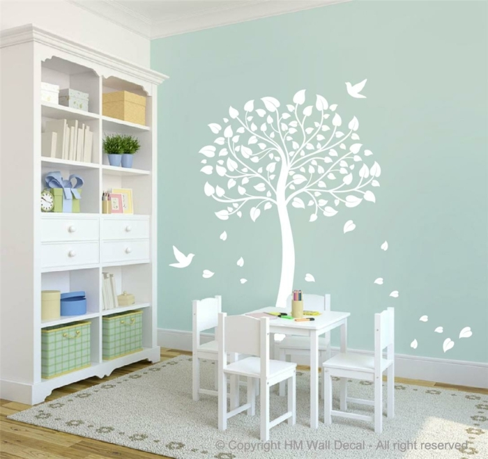 vinilos decorativos, habitación infantil con mini mesa blanca, pared azul con vinilo blanco de árbol y pájaros