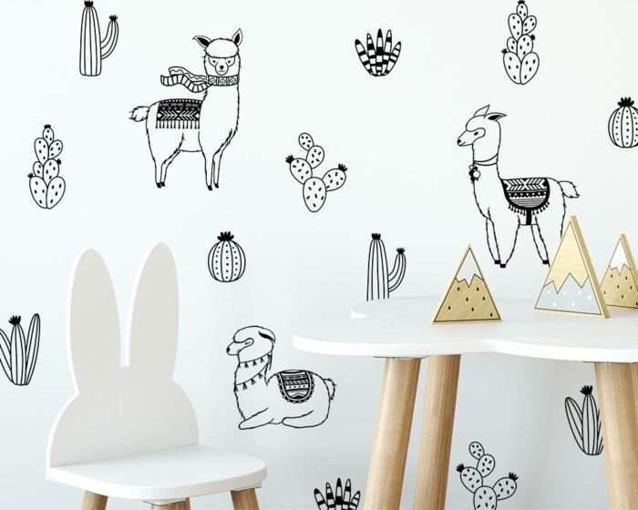 vinilos decorativos, mesita y silla infantiles en blanco, pared con múltiples vinilos, llamas en diferentes posiciones y cactus