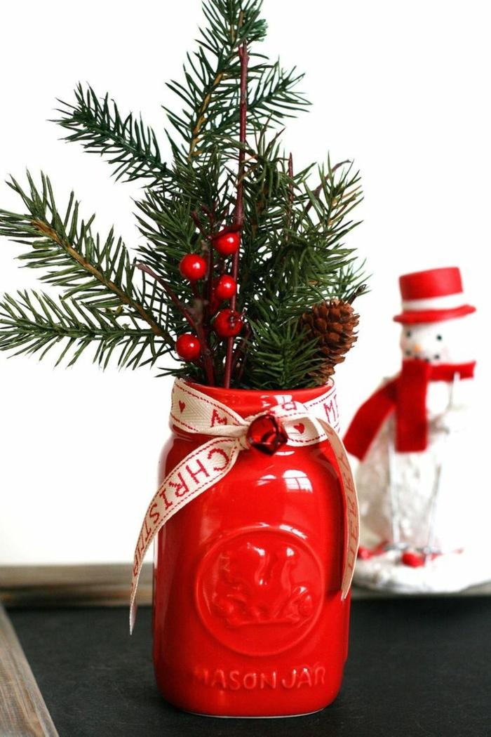 centros navideños, frasco decorativo pintado en rojo lleno de ramas de pino y acebo, figura decorativa de monigote de nieve