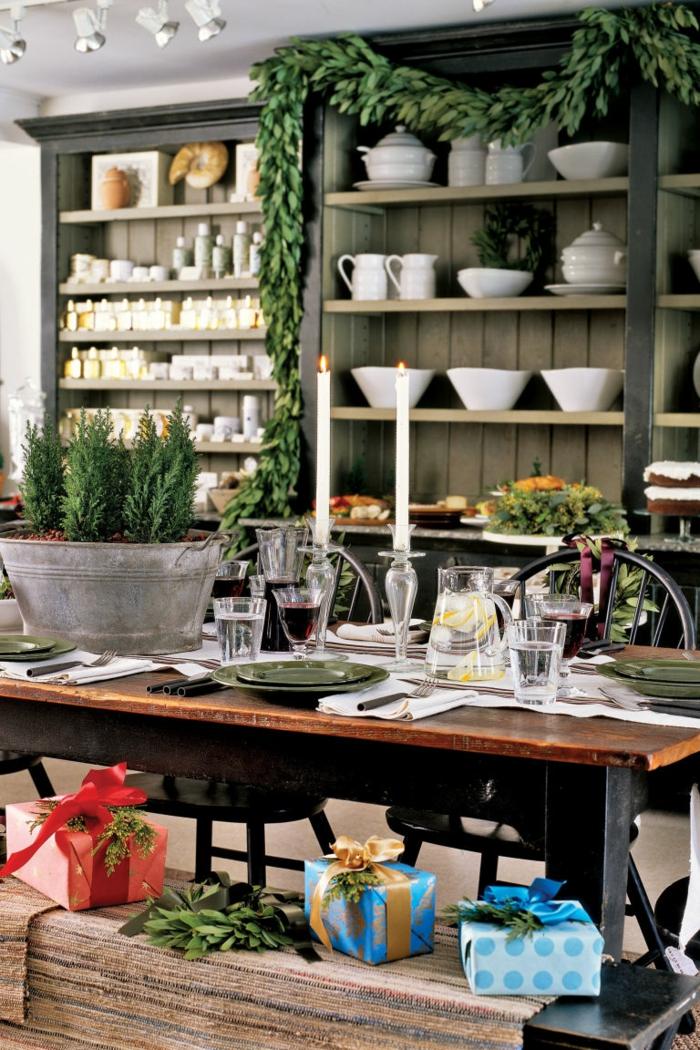 centro de mesa, comedor en estilo rústico, decoración en verde, centro de mesa con pinos enanos en un macetero de metal, regalos puestos en el banco de madera