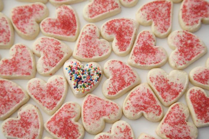 receta de galletas de mantequilla, pequeñas galletas en forma de corazón con chispas de azúcar en diferentes colores