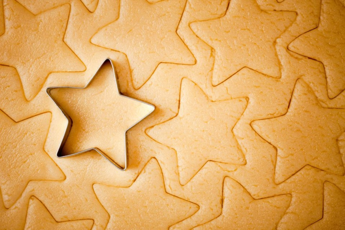 receta de galletas de mantequilla, galletas de navidad con la forma de estrella, cortar las piezas con cortador de galletas