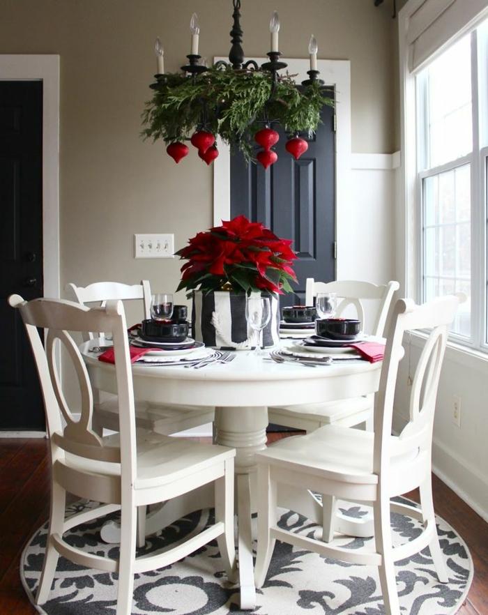 centros de mesa navideños, comedor blanco con detalles en rojo, estrella de navidad en la mesa, candelabro decorado de ramas de pino y ornamentos rojos