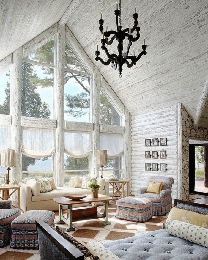cabañas de madera, interior en blanco con detalles en tonos pastel, candelabro negro vintage, cama azul en capitoné