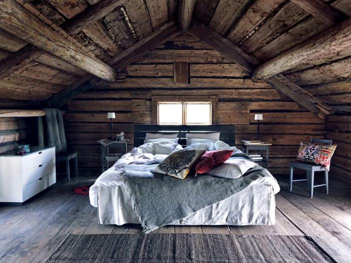cabañas de madera, dormitorio acogedor en una buhardilla, techo, paredes y suelo de madera, cama doble con cabecero de vigas