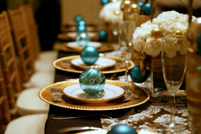 centros de mesa, flores blancas en el centro de la mesa en jarrones de vidrio, bolas en azul reluciente en los platos
