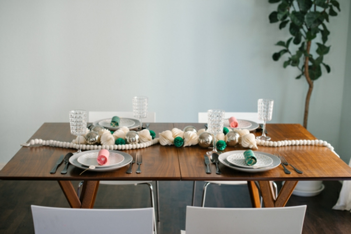 centros de mesa originales, mesa de madera simple con decoración refinada de ornamentos de papel y guirnalda de bolas pequñas