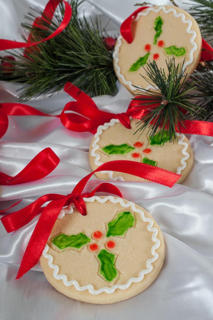 galletas navideñas, galletas de mantequilla con decoración de acebo y cintas rojas para adornar el árbol de navidad
