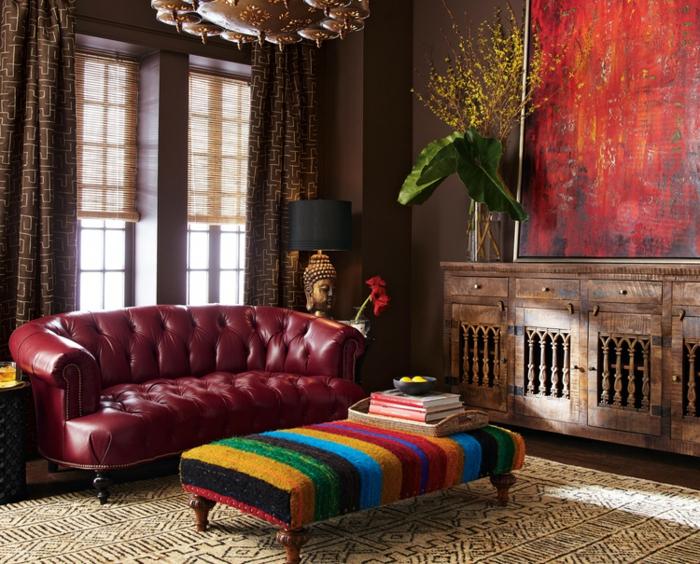 salones modernos, sofá en color bordeos, tapizado con piel en capitoné, grande pintura decorativa, banco en estilo bohemio