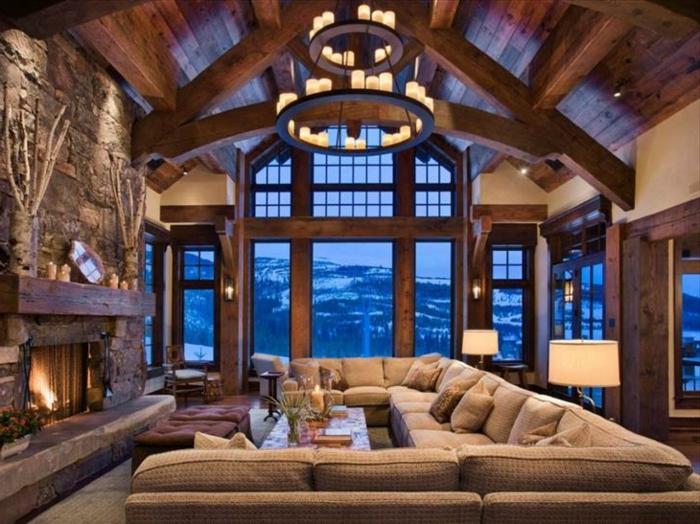 casa de madera, precioso salón con candelabro vintage, grande sofá en beige y paredes de piedra, vista a la montaña