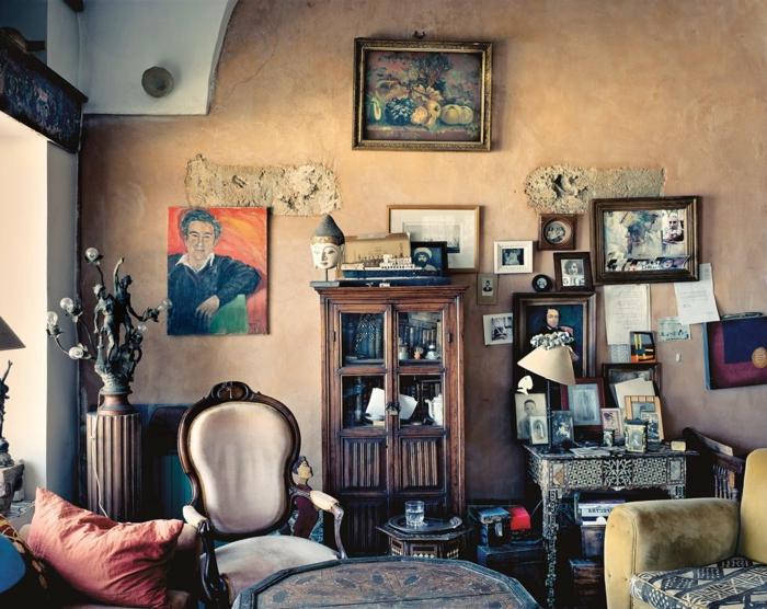 muebles de salon, salón vintage con toque bohemio, paredes en color ocre anaranjado, muchas pinturas en las paredes