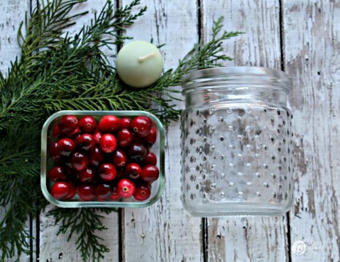 centros de navidad, manualidades faciles para navidad hechas con acebo, frasco de vidrio lleno de ramas de pino y acebo