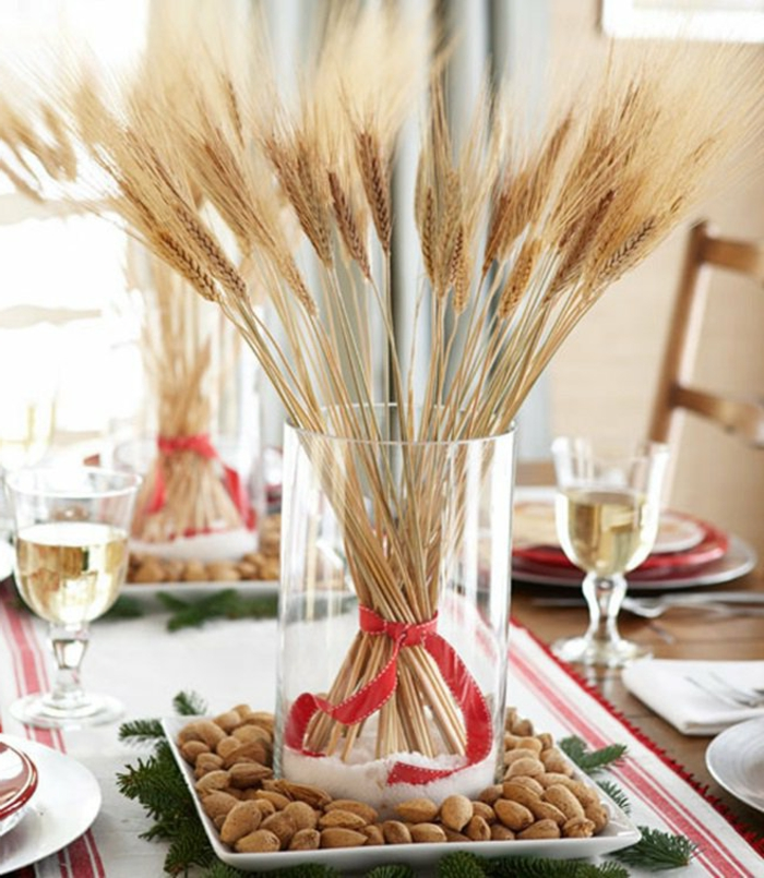 centros de mesa navideños, idea simple y económica con ramo de trigo seco y ramas de pino, cubierta en blanco con bordes en rojo