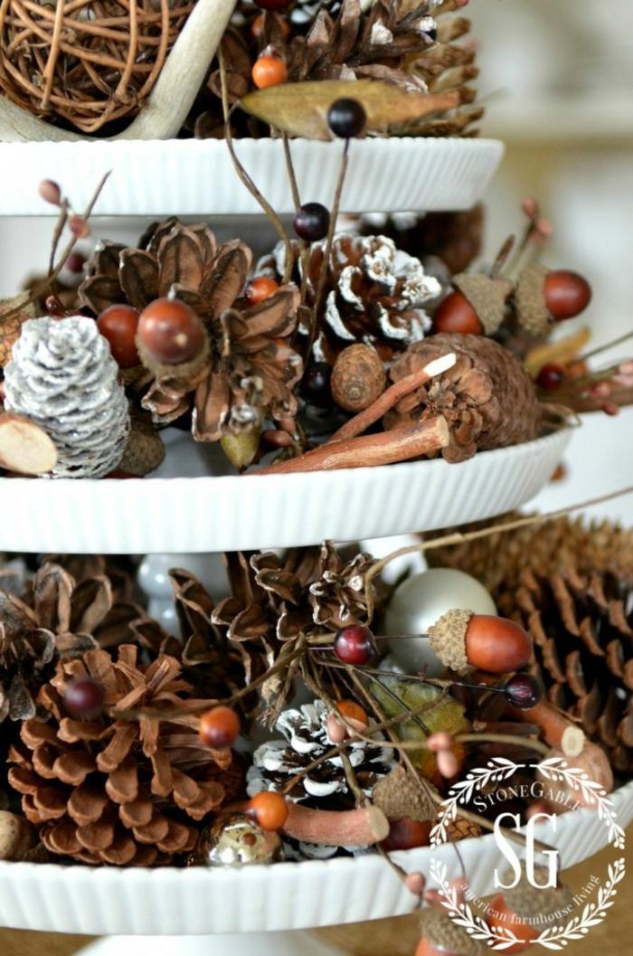 centros de navidad, centro de mesa en forma de tarta en tres niveles, decoración de piñas y frutas secas