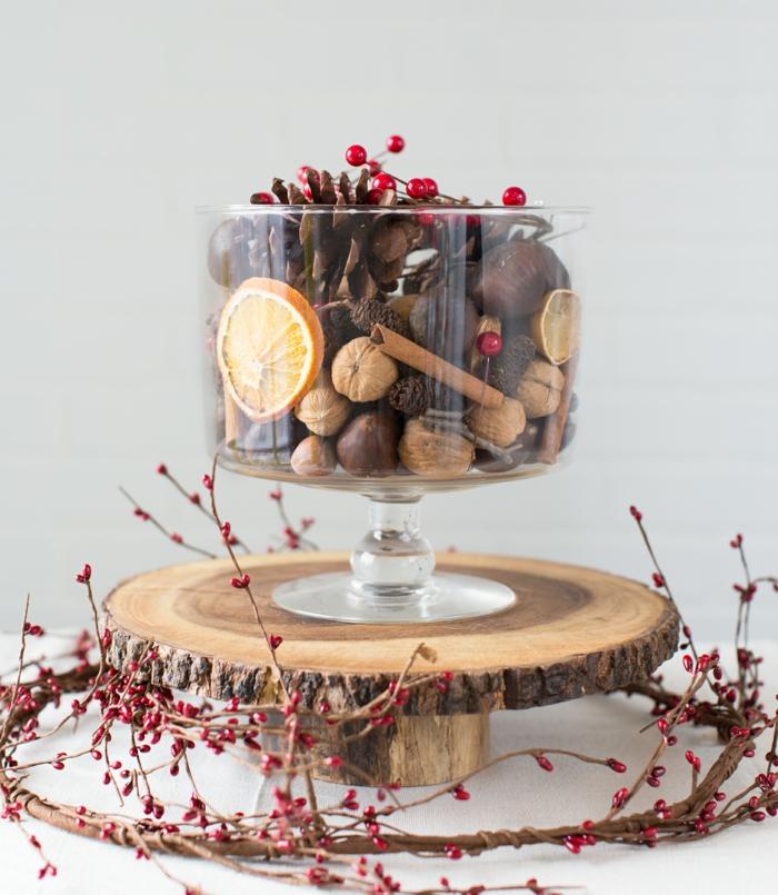 centros de navidad, ideas DIY, frutas secas, palos de canela y acebo artificial en un recipiente de vidrio, centro de mesa atractivo