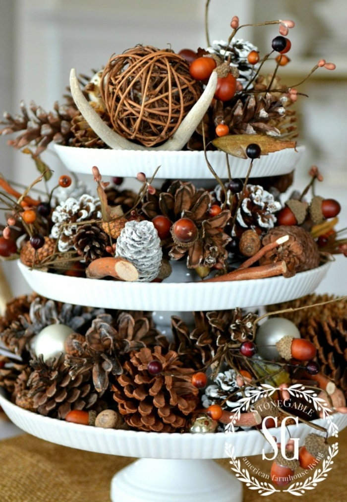 centros de mesa navideños, idea original con muchas piñas y otros materiales naturales secos, centro de navidad en tres niveles